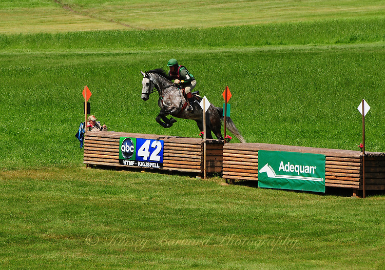 Horse and rider cross country jumping a The Event at Rebecca Farm Kalispell Montana. Beautiful Montana scenery provides a beautiful backdrop for beautiful rider and horse athletes as they navigate and extraordinary cross country race course.