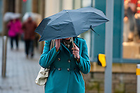 Friday 31 January 2014<br /> Pictured: A woman walks through Carmarthen town centre clutching an umbrella<br /> Re: Severe weather warnings are issued accross Wales and England