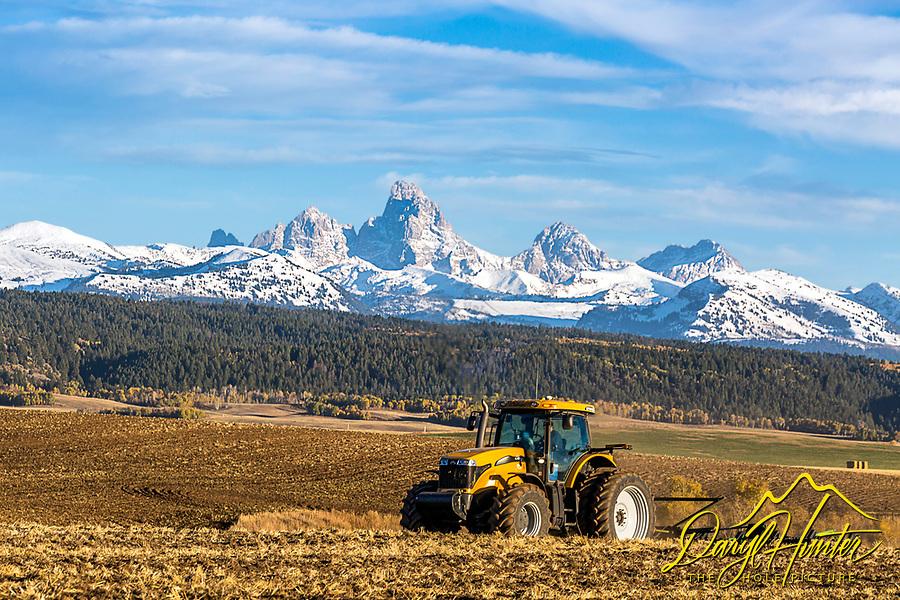 A farmer tills his field under the crowning Grand Tetons of Teton Valley Idaho