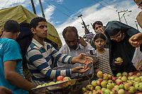 Srinagar, India-August 8, 2010: A Kashmiri fruit vendor attends his customers during a temporary lifting of a curfew in downtown Srinagar