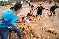 En la invasión Laura Alicia Frías vecinos de ese lugar hicieron una cadena para poder ayudar a cruzar a las personas por el canal crecido por la fuerte lluvia que azoto al norte en la foto la sra. Balu Zazueta le pasan el mandado y después ella aunque con un poco de problemas por la fuerte corriente.