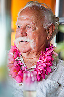 A man wearing a pink plumeria lei on his birthday