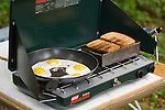 Camping stove cooking eggs and toast.
