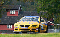 The #94 BMW of Bill Auberlen and Paul Dalla Lana races past a red building during the Grand-Am Rolex Series test at Virginia International Raceway, Alton, VA , October 2010. (Photo by Brian Cleary/www.bcpix.com)