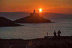 Swansea, UK, 25th March 2020.<br />A couple watch the stunning sunrise over the Mumbles Lighthouse near Swansea today as government warnings continue to ask people to stay at home due to the Coronavirus outbreak in the UK.