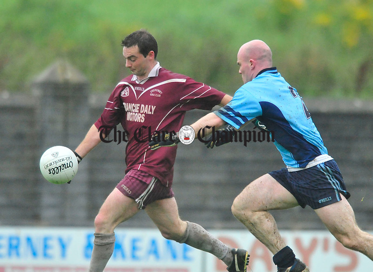 Alan Nagle of Lissycasey pressured by Cooraclare's Bob Chambers. Photograph by Declan Monaghan