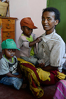 MADAGASCAR, Mananjary, canal des Pangalanes, village AMBOHITSARA, tribe ANTAMBAHOAKA, fady or taboo, according to the rules of their ancestors twin children are a taboo and not accepted in the society / MADAGASKAR, Mananjary, Dorf AMBOHITSARA, Zwillinge sind nach dem Ahnenkult ein Fady oder Tabu beim Stamm der ANTAMBAHOAKA, Frau CHRISTINE MANAMPETRA mit Zwillingen ROLAND - orange Kappe - und CEDRICE - gruene Kappe