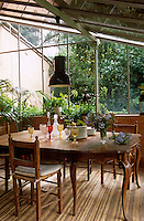 An industrial-style pendant light hangs above an elegant dining table laid with coloured wine glasses and piles of dinner plates in this conservatory dining room