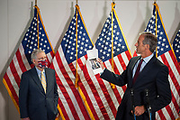 United States Senator John Thune (Republican of South Dakota), holds up news articles relating to the Russia Taliban bounty story as he is joined by US Senate Majority Leader Mitch McConnell (Republican of Kentucky), left, and other Senate GOP leadership as he fields questions from reporters following the GOP luncheon in the Hart Senate Office Building on Capitol Hill in Washington, DC., Tuesday, June 30, 2020. Credit: Rod Lamkey / CNP /MediaPunch