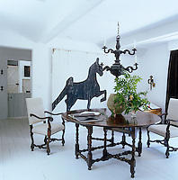 The focal point of the dining room is the large antique barn door with a naive painting of a horse in simple black-and-white