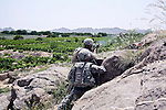 A soldier with Company A, 2nd Battalion, 2nd Infantry Regiment fires a grenade at a Taliban position after his patrol is attacked near the village of Zangabad in Panjwayi district, Kandahar province, Afghanistan. April 27, 2009. DREW BROWN/STARS AND STRIPES