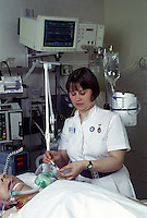 Intensive care unit Nurse putting medicine into a patient's drip using a syringe.