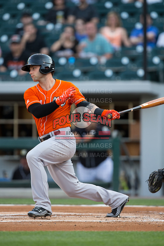 Christian Walker (14) of the Norfolk Tides follows through on his swing against the Charlotte Knights at BB&T BallPark on April 20, 2016 in Charlotte, North Carolina.  The Knights defeated the Tides 6-3.  (Brian Westerholt/Four Seam Images)
