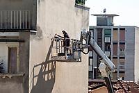 Milano, quartiere Bovisa, periferia nord. Un uomo su piattaforma aerea effettua lavori di manutenzione ad un edificio --- Milan, Bovisa district, north periphery. A man on aerial platform performing maintenance work at a building