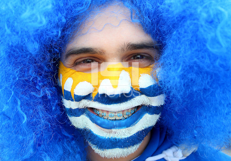 A Uruguay fan with painted face, blue wig and blue braces on his teeth outside Arena Corinthians