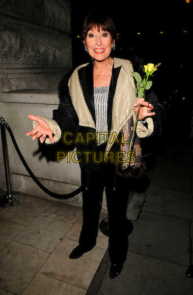 """ANITA HARRIS .The """"I'd Like To Teach The World To Sing"""" tribute concert afterparty, Mint Leaf  bar & restaurant, London, England..February 24th, 2008.after party full length black cream coat jacket fur trim yellow rose flower hands .CAP/CAN.©Can Nguyen/Capital Pictures."""