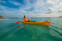 Maldives, Rangali Island. Conrad Hilton Resort. Woman kayaking on the Indian ocean, near the beach and palm tree.