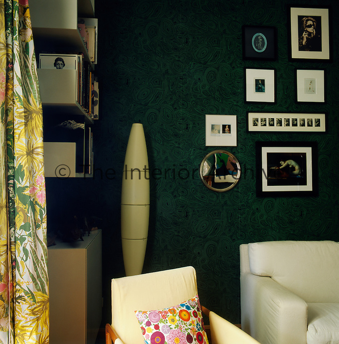 The sitting room, with its green and black pattern wallpaper and eclectic items, combines pieces of Fifties and Sixties vintage furniture with neo-pop décor.