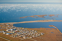 Aerial view of the Inupiat native village of Kaktovik, on Barter Island, in the Beaufort Sea along Alaska's arctic coast. Sea ice dots the waters in the distance.