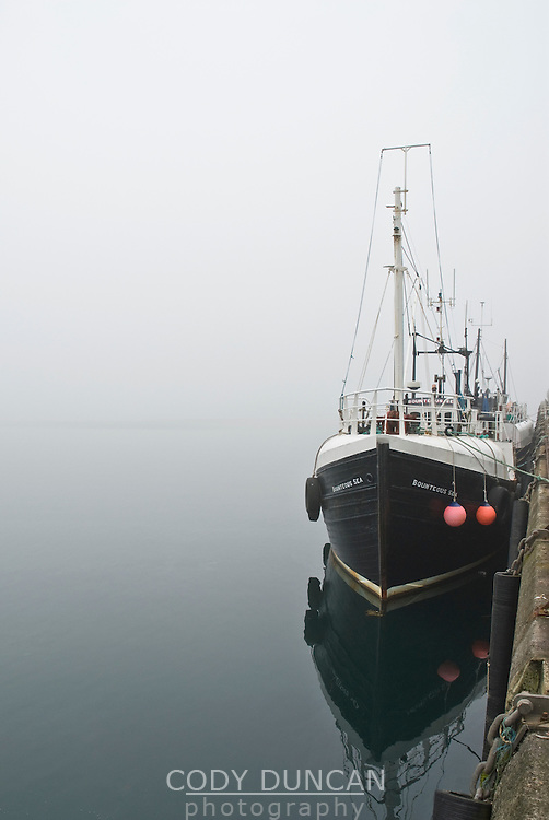 Fishing boat sitting at port in dense fog, Stromness, Orkney, Scotland