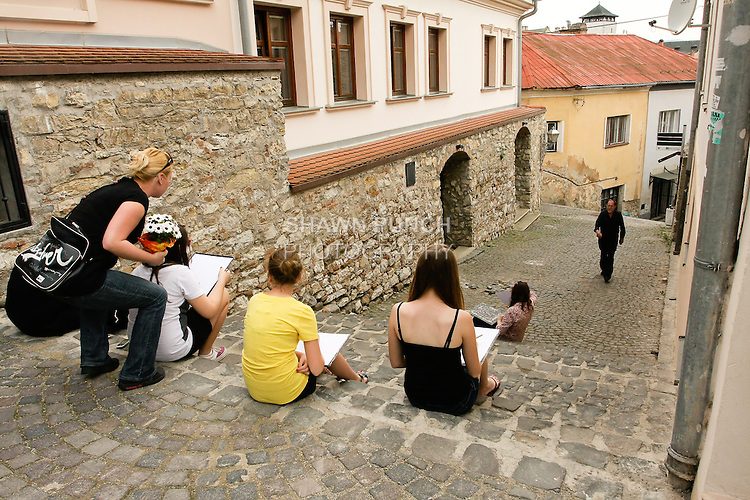 Art students sitting on steps and drawing.
