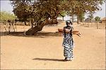 Le ramassage du bois utilisé principalement comme combustible détruit la forêt et favorise l'avancée du désert / Il est important de sensibiliser les personnes sur ce risque et de trouver d'autres combustibles de substitution - ce que fait le PADB Programme d'Aide au Développement du Brakna Sud / Reportage dans la région du Brakna Sud sur la sécurité alimentaire et le programme PADB financé par l'UE / Mauritanie / Afrique / Young woman carrying wood logs for kitchen fire in Mauritania / This practice damage the remaining forest / PADB South Brakna Development Program financed by the European Union / Mauritania / Africa