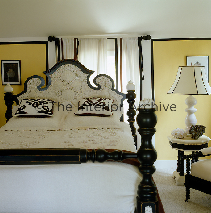 Vibrant yellow walls provide a backdrop to the striking black-and-white bed with an ornate shell-encrusted headboard