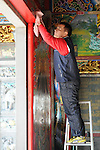 Bao-jhong Yi-min Temple, Kaohsiung -- Paintings on the main temple door being cleaned.