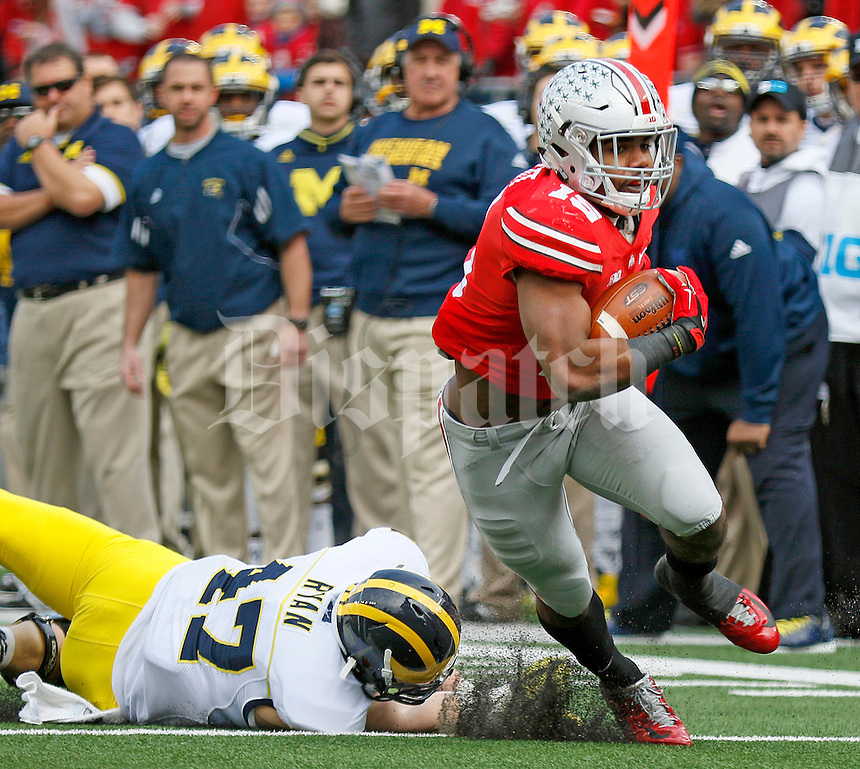 Ohio State Buckeyes running back Ezekiel Elliott (15) gets away from Michigan Wolverines linebacker Jake Ryan (47) during the first quarter of the NCAA football game against Michigan at Ohio Stadium on Saturday, November 29, 2014. (Columbus Dispatch photo by Jonathan Quilter)