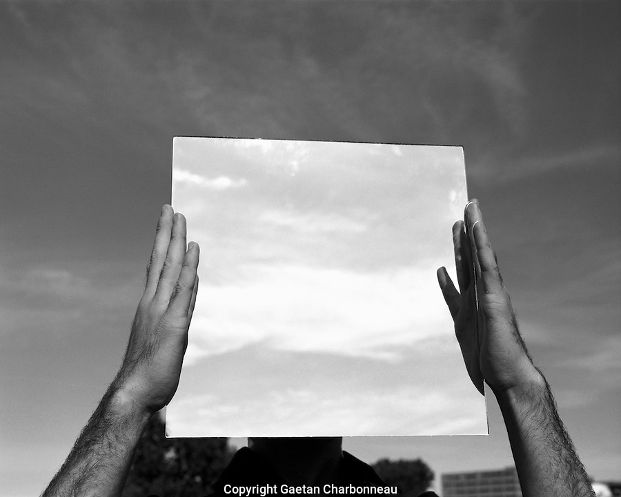 A man holding a mirror in front of his face.