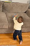 10 month old baby boy pulling self to stand in order to reach toy on couch