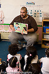 Preschool 4-5 year olds male teacher showing page of picture book to group of children reading to them vertical