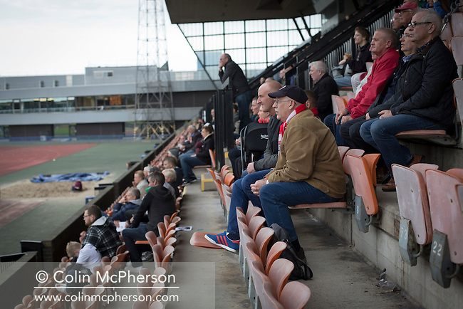 Away supporters watching the first-half action at Meadowbank Stadium in Edinburgh, as Edinburgh City (in white) played host to Spartans in a Lowland League fixture. The host won the match 1-0 with a late goal by Ousman See, despite playing for the last 30 minutes with 10 men after Ross Allum was sent off. The wind kept the reigning champions side clear at the top of the league.