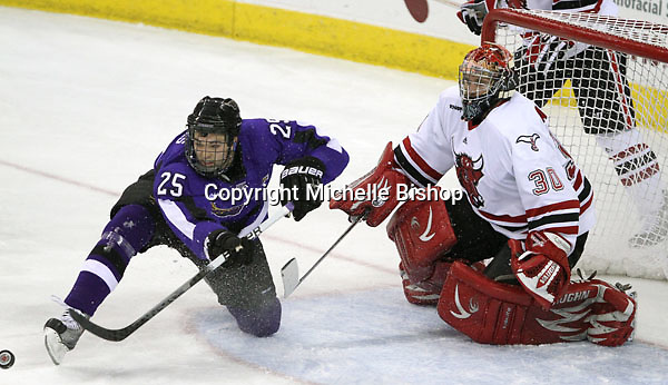 Minnesota State University-Mankato's Eriah Hayes eyes a loose puck as UNO goalie John Faulkner looks on. (Photo by Michelle Bishop)