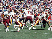 Washington Redskins running back Joe Washington (25) carries the ball after taking a hand-off from quarterback Joe Theismann (7) during the game against the San Francisco Forty-Niners at RFK Stadium in Washington, D.C. on October 4, 1981.  Blocking for Washington are tackle Mark May (73) and Ron Saul (64).  The 49ers won the game 30 - 17. <br /> Credit: Howard L. Sachs / CNP