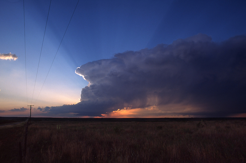 A rotating severe thunderstorm, known as a supercell, is sillouetted by the setting sun near Jayton Texas in May. This storm produced hail to the size of tennis balls.