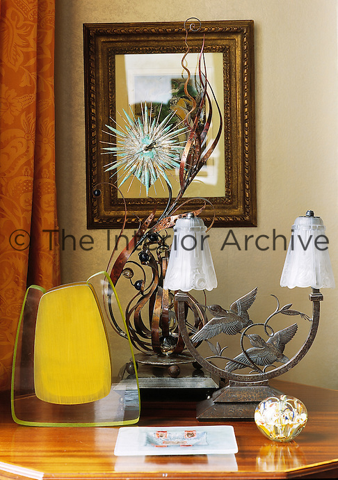 A display of contemporary objects on a wooden table including a metal table lamp, a yellow sculpture and a bronze sculpture.