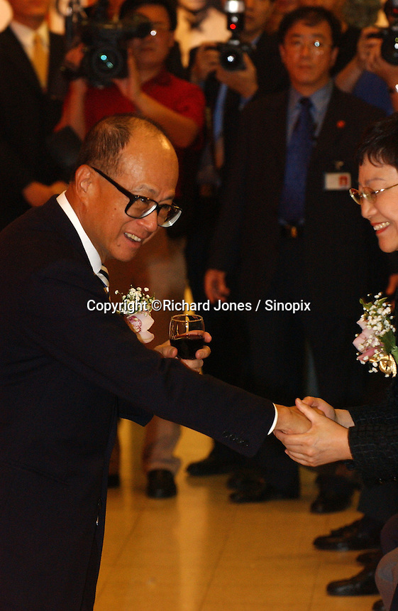 Li Ka Shing shakes hand with Deng's youngest daughter, Deng Rong at the opening ceremony of &quot;Giant of the Century&quot; - an exhibition to commemorate the 100th Anniversary of the Birth of Deng Xiaoping in Hong Kong. The exhibition aims at introducing Deng's life to the people of Hong Kong.<br /> 26-AUG-04