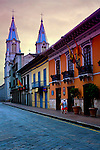 The spires of Iglesia de San Alfonso rise above the colorful colonial architecture of Cuenca, Ecuador and a lone woman delivering early morning bread.  The city center is listed as a UNESCO World Heritage Trust Site.