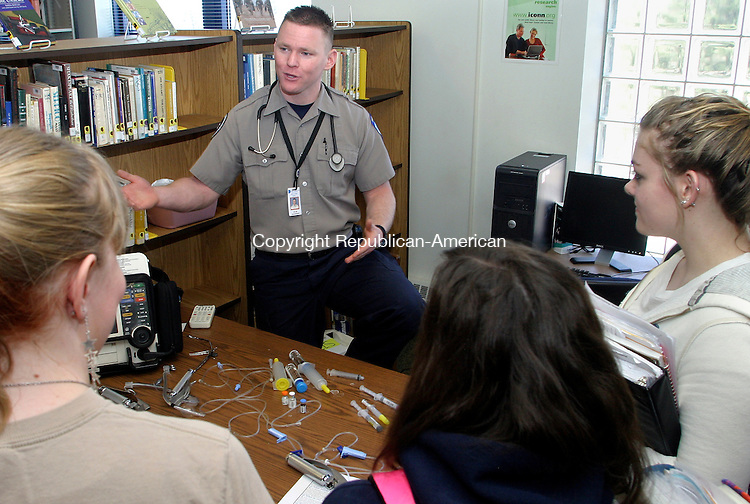 WOODBURY, CT.- 13 MARCH 2009-031309DA02-Paramedic for Danbury Health Systems, Blair Balmforth talks with students of Nonnewaug High School in Woodbury, from left, Emily Cornwell, Kiley Orosz, and Nicole Dinsmoor during a career fair held in the school's library Friday. <br />  Darlene Douty Republican-American