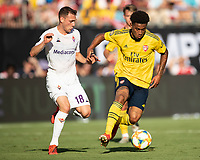 CHARLOTTE, NC - JULY 20: Reiss Nelson #24 advances against Sebastian Cristoforo #18 during a game between ACF Fiorentina and Arsenal at Bank of America Stadium on July 20, 2019 in Charlotte, North Carolina.