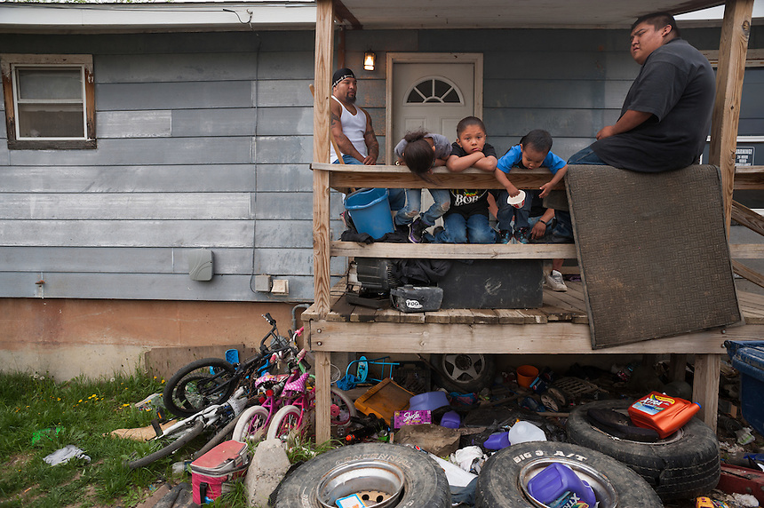 Travis Brien, left, and family sit on the porch of their home on the Crow Reservation at Crow Agency, Montana, Thursday, May 16, 2013. Pending new ports for shipment to Asia through either the U.S. or Canada, Cloud Peak Energey hopes to open new high-grade coal mines on and near the Crow Reservation in southern Montana. The tribe is equally hopeful the new mines would bring long-awaited economic stability to the tribe. (Kevin Moloney for the New York Times)