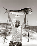 USA, Florida, man on boat holding up the catch of the day, Mahi Mahi, Islamorada (B&W)