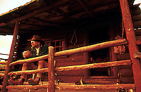 A man sits on the porch of an old log cabin.