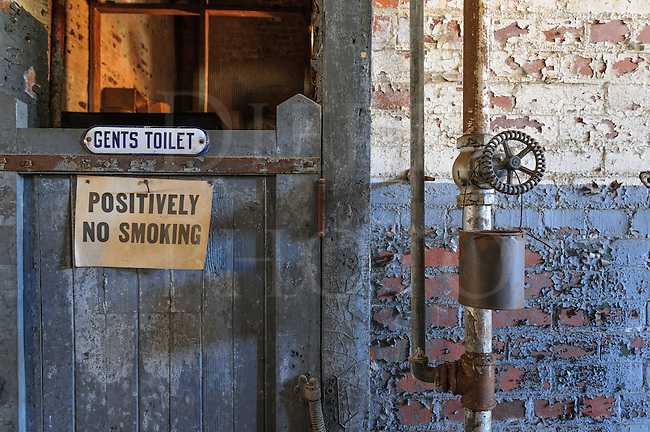 Old men's room bathroom door closed, flaking and peeling paint in industrial grunge factory setting.
