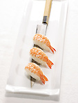 Three pieces of shrimp sushi on a long Japanese wood-handled knife