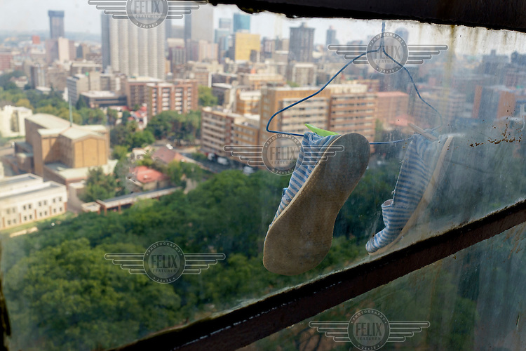 A pair of slippers hangs out of a window in Highrise, a 19-storey residential tower overlooking a park in Hillbrow, Johannesburg's most notorious neighbourhood. Once a preserve of middle-class whites it is now overcrowded, ridden with illegal squats and suffers from high levels of crime, much of which is related the thriving illicit drug trade.