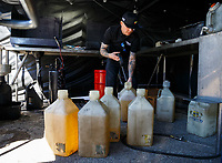 Mar 17, 2018; Gainesville, FL, USA; NHRA funny car driver Jonnie Lindberg mixes containers full of nitro methane racing fuel in the pits during qualifying for the Gatornationals at Gainesville Raceway. Mandatory Credit: Mark J. Rebilas-USA TODAY Sports
