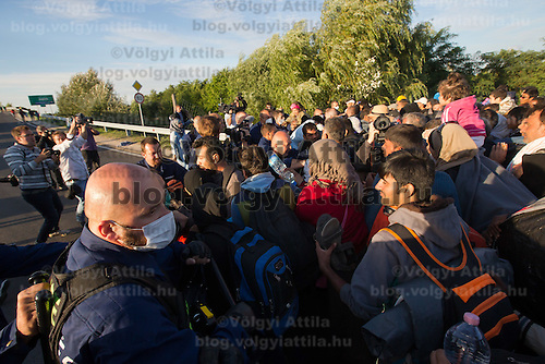 Illegal migrants try to break out and run away from custody through a line of police officers near Roszke (about 174 km South of capital city Budapest), Hungary on September 07, 2015. ATTILA VOLGYI