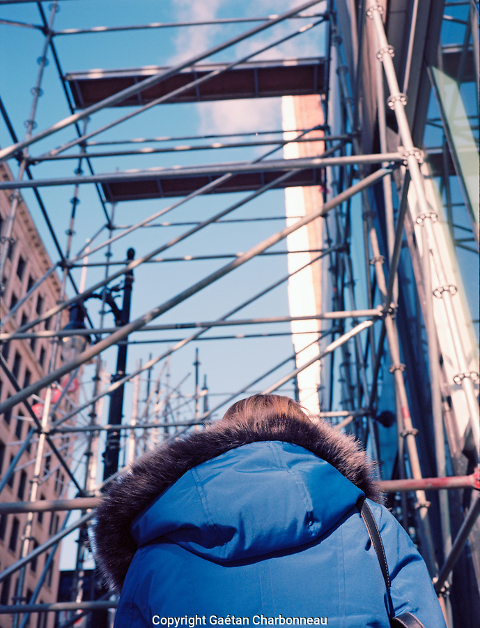 Woman walking underneath scaffold